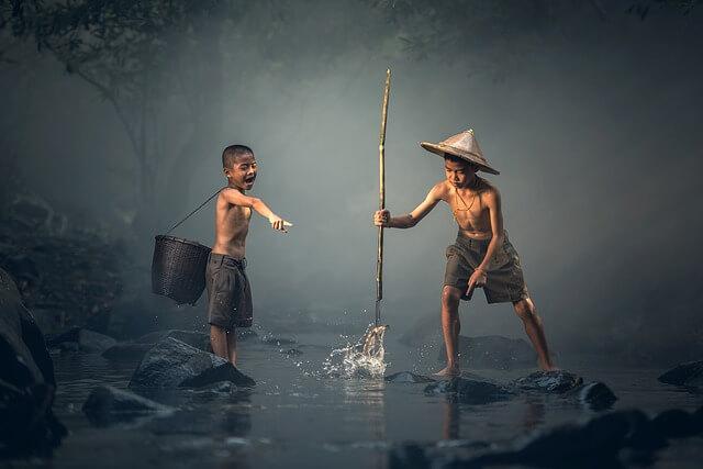 魚を捕まえる子供とみている子供