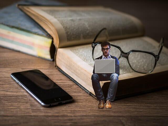 マニュアルの上でパソコンで学ぶ男性