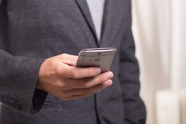 スマートフォンでトレードする男性